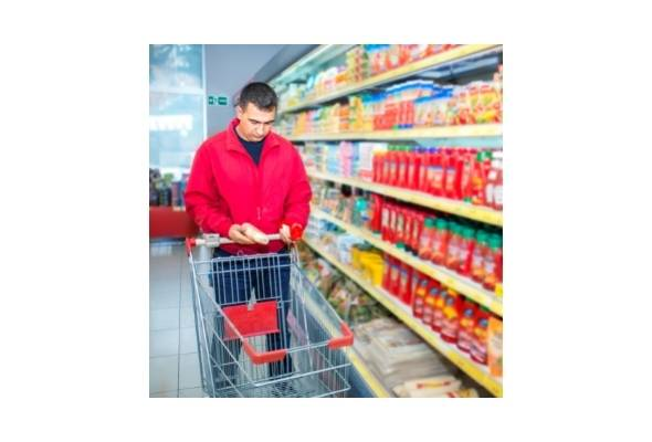 Merchandising Refrigerators, a male shopper in the grocery store comparing products